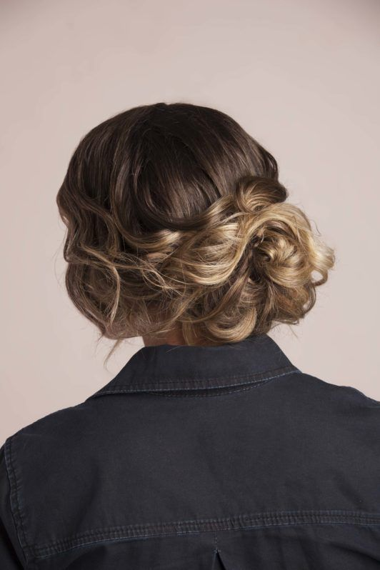 Model shows how to do a messy bun with curls