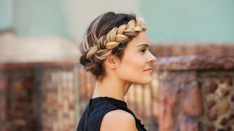 blonde woman with a halo braid standing to the side