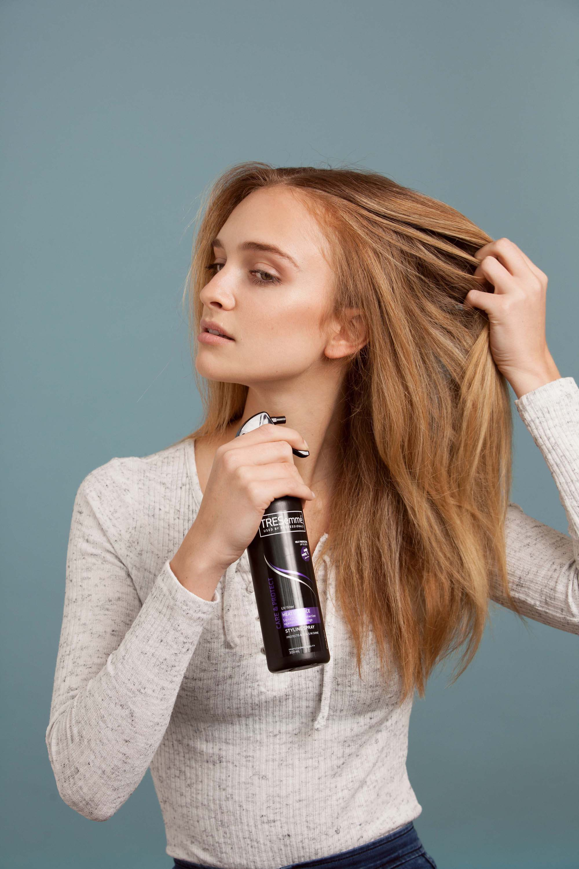 Blonde woman holding her hair and spraying heat protect spray