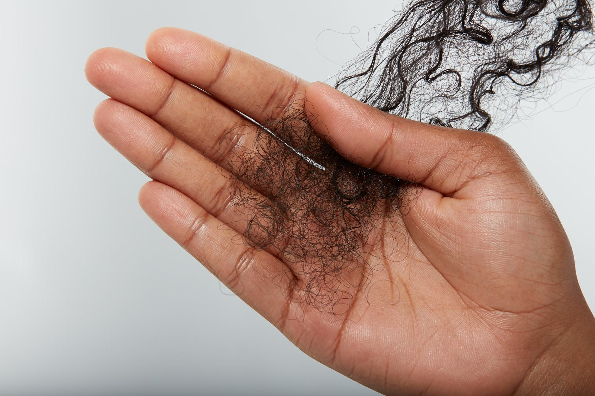 Close-up of a hand holding frizzy natural hair