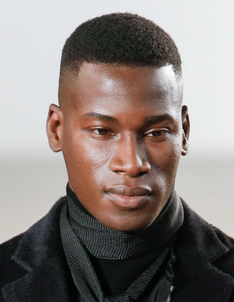 black man on the runway with a high fade hairstyle wearing dark clothing
