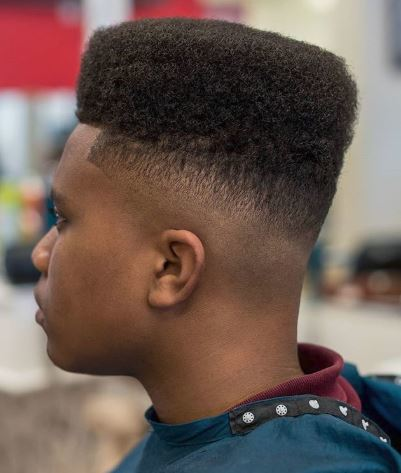 High top fade: Black man with square top fade haircut in barber chair.