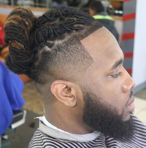 High top fade: Black man in barber chair with dark brown and golden brown twists in a high bun and long beard.