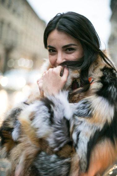 Hot oil treatment: Woman with long dark brown tousled hair, wearing big fluffy jacket outside