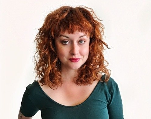 woman with curly hair and bright copper red hair