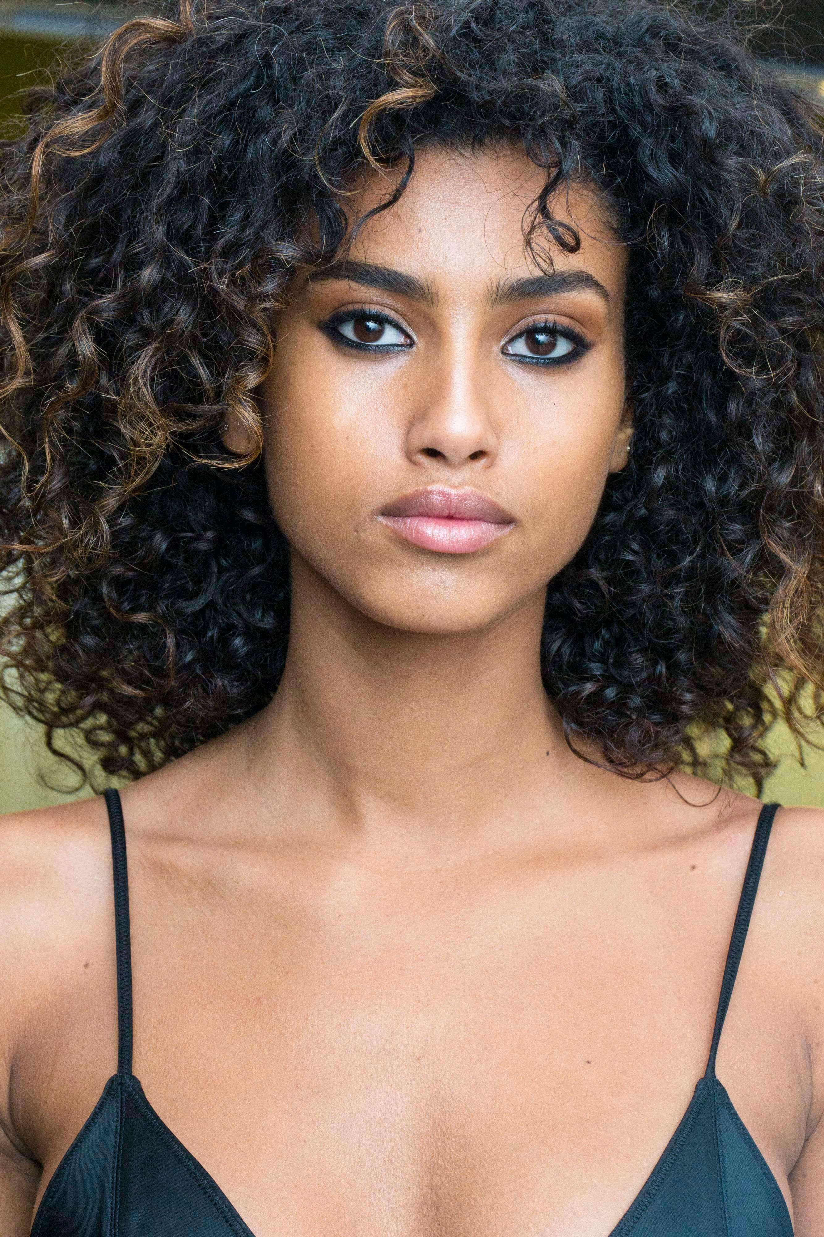hairstyles for round faces: Black woman with brown curly hair