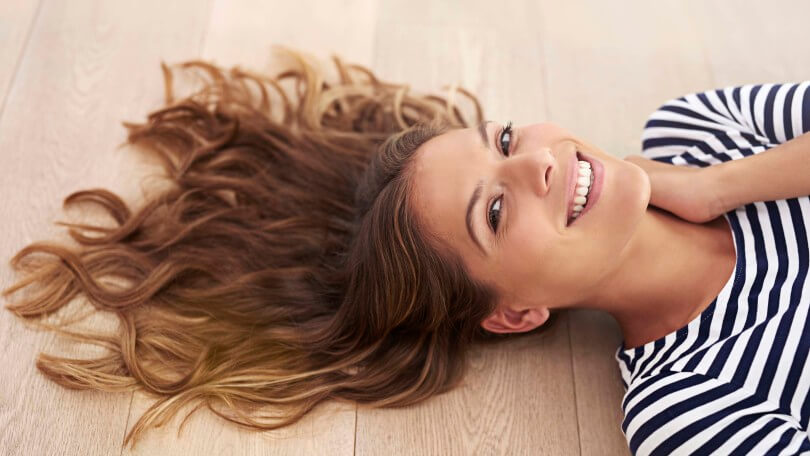a brunette girl with wavy hair lying down at the floor smiling at the camera