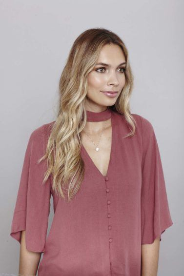 model with loose wavy curls wearing pink shirt