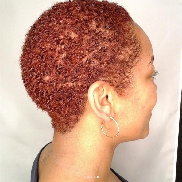 woman with a small afro haircut and a deep copper hair colour
