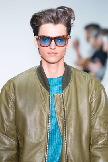 male model on the runway wearing a blue tshirt under a khaki coloured leather jacket and wearing sunglasses with his medium brunette hair worn in a relaxed quiff