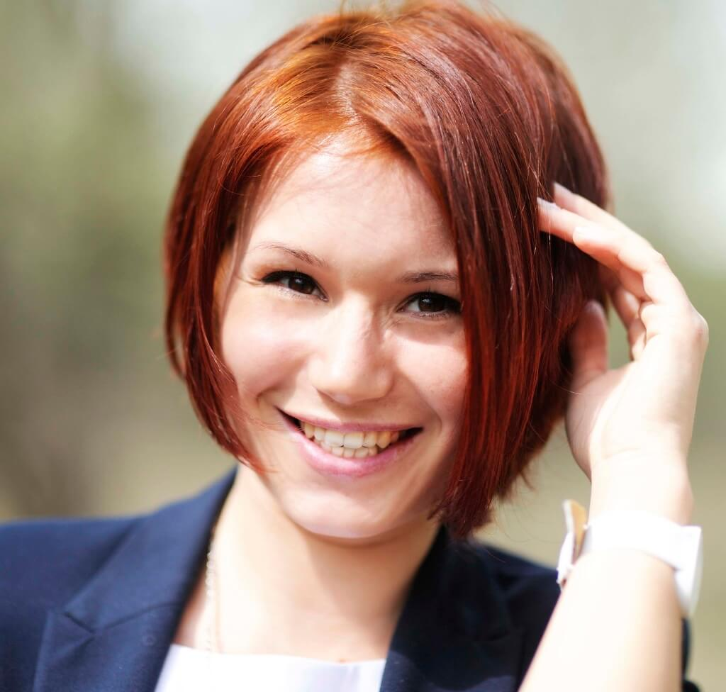 Red haired woman with an angled bob haircut, touching her hair with her hands.