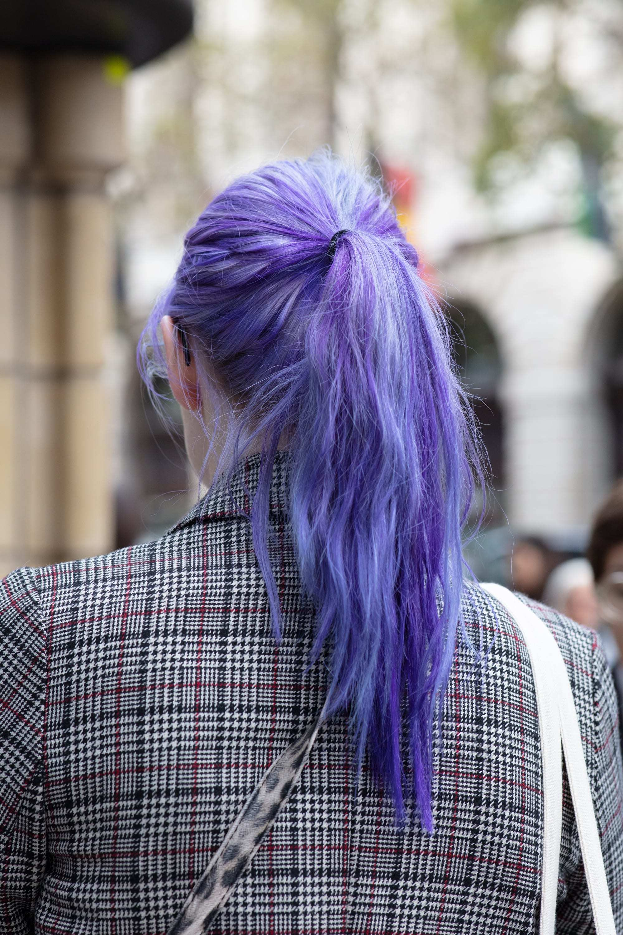 Hot oil treatment damaged hair: Woman with purple low ponytail, wearing checked blazer outside