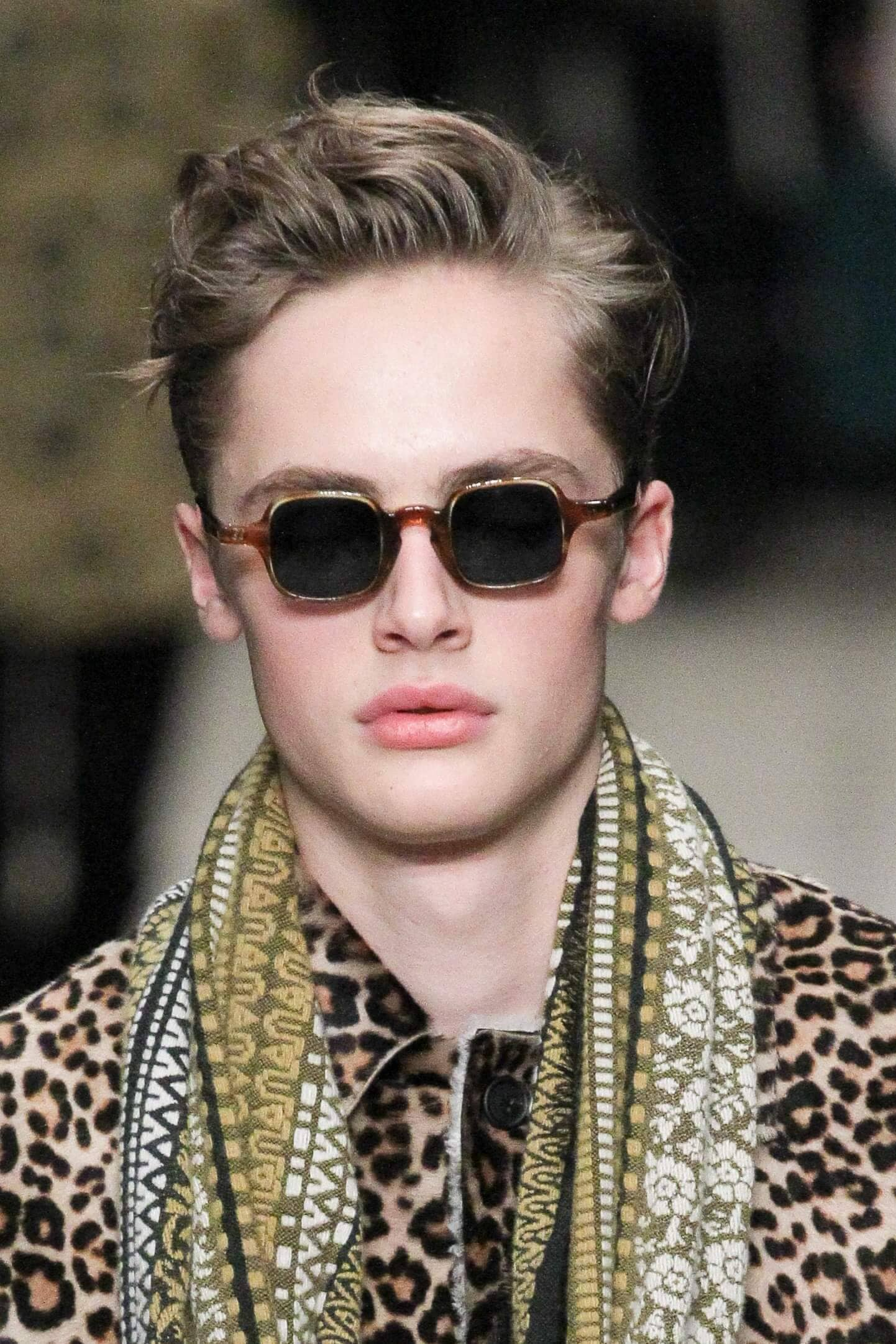 male model with dark blonde pushed back hair with a side parting