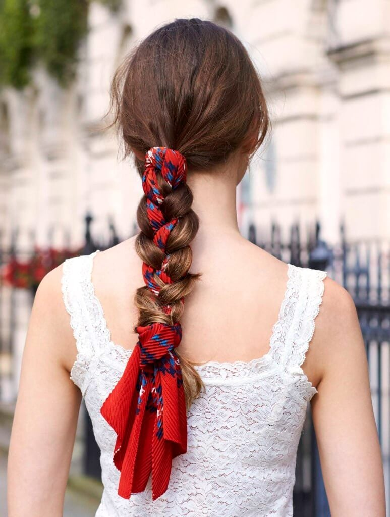 back view of a woman with brown long hair with a scarf woven braid
