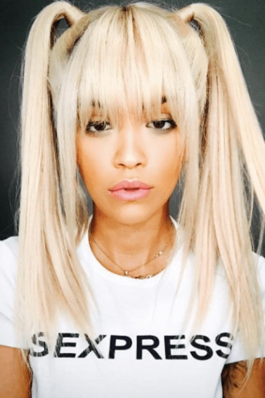 front facing image of Rita Ora with blonde hair in pigtails and a full fringe with platinum blonde hair