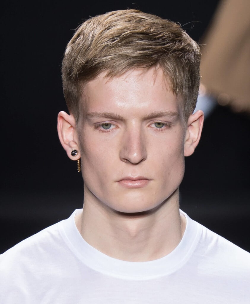 male model on the runway wearing a white top and an earring with his dirty blonde hair worn in a neat crop