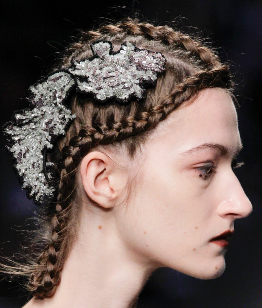 side view of a young model with multiple braids and a glittery hair accessory