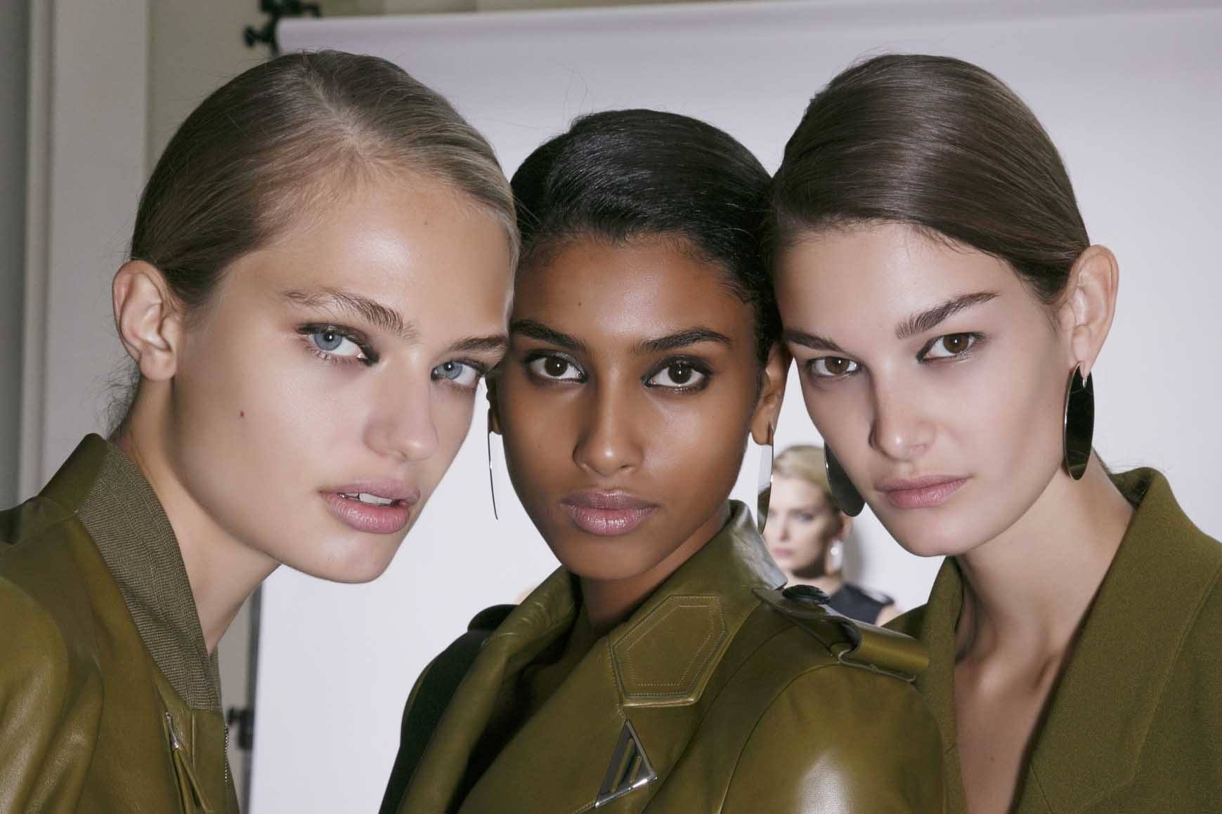 keratin hair treatment Q&A: close up shot of three models with sleek, smooth hair, wearing all green and posing backstage at a fashion show