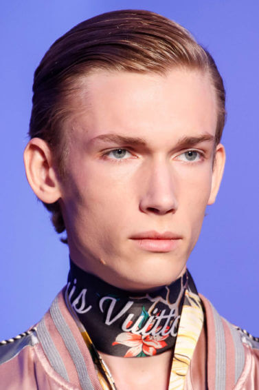 male model walking on the Louis Vuitton runway wearing a colourful outfit with his blonde hair slicked back