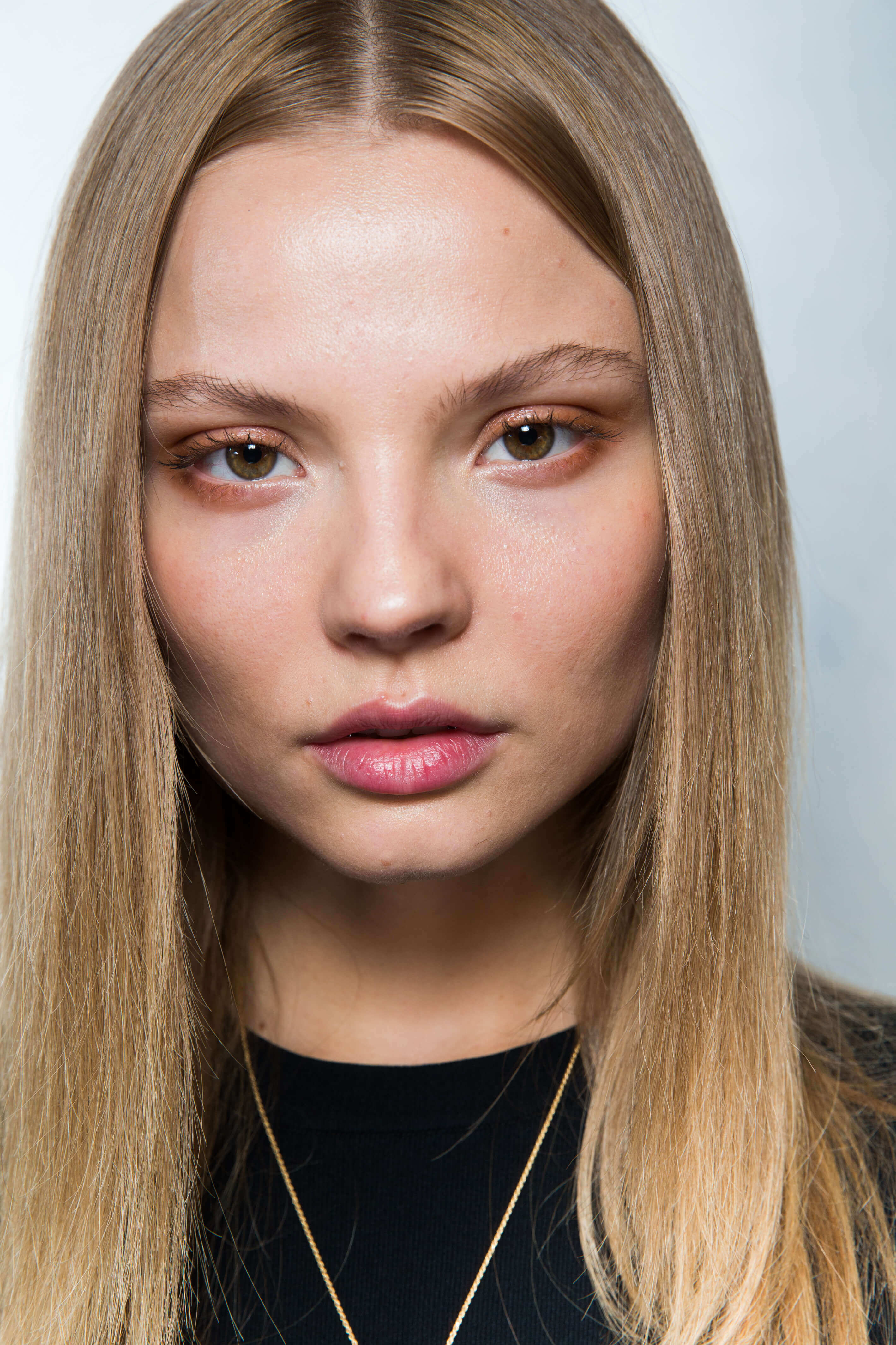 keratin hair treatment: close up shot of model with straight, long dark blonde hair. posing backstage at a fashion show