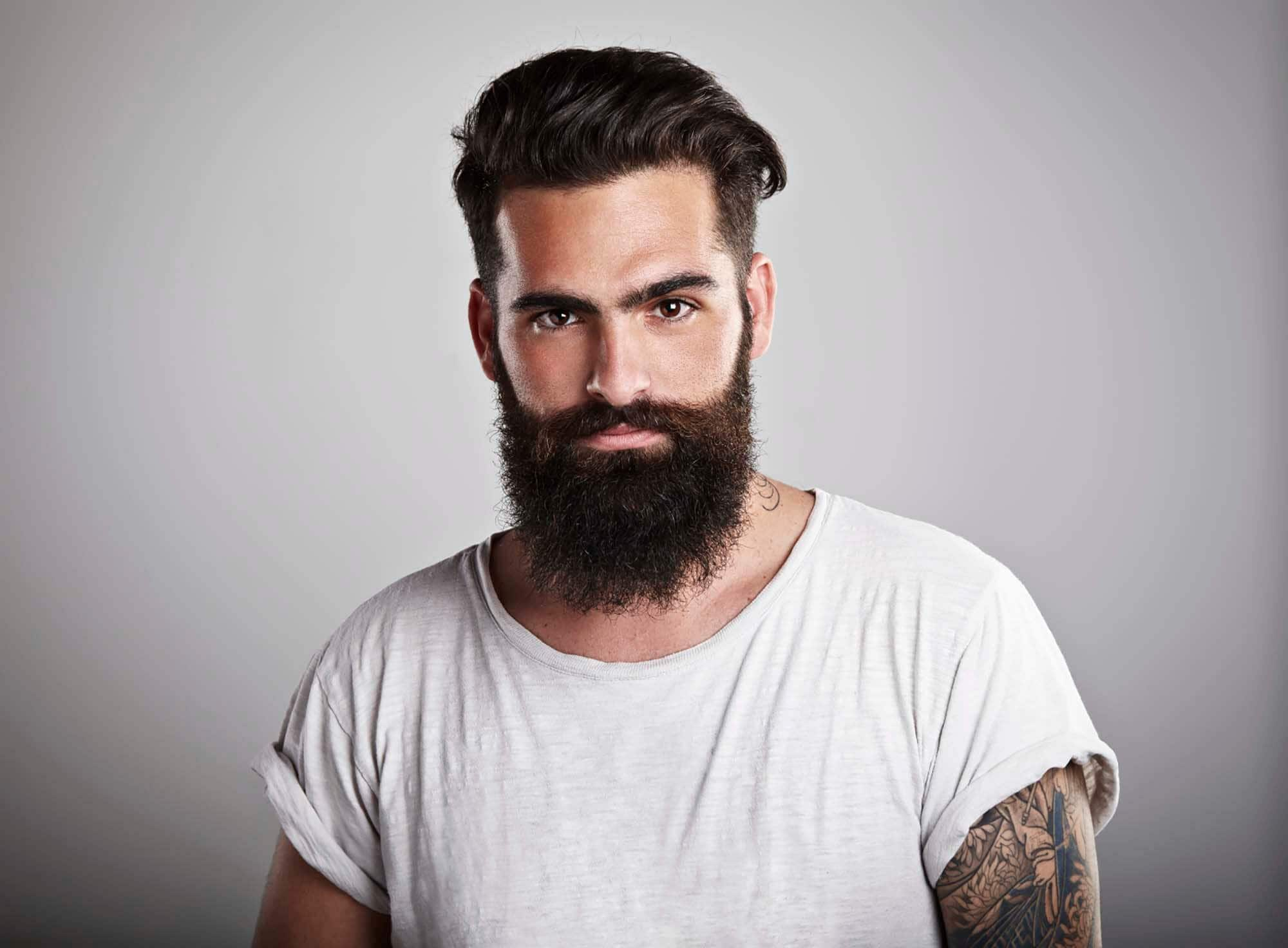 undercut hairstyle: dark haired man with beard
