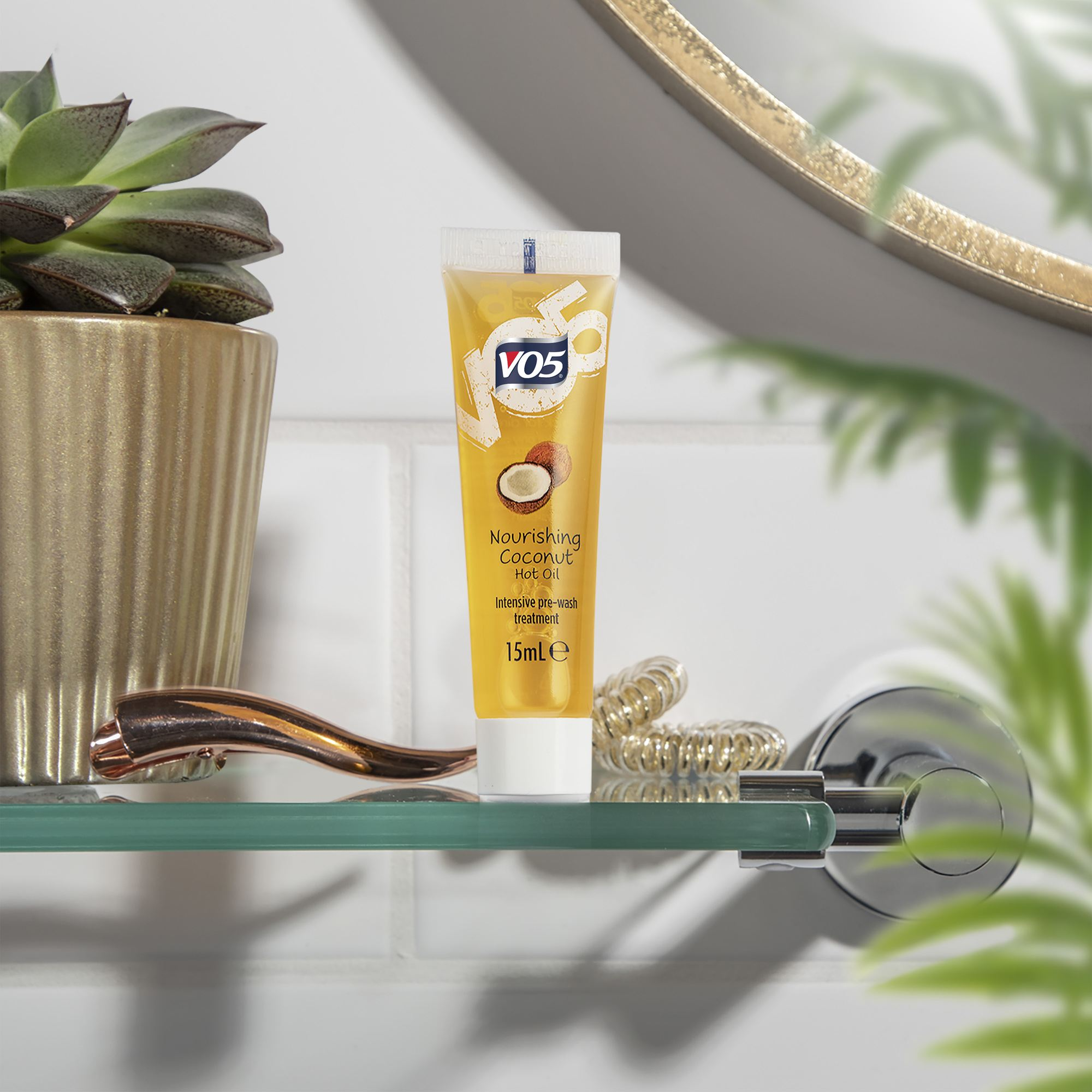 Hot oil treatments: Shot of the VO5 Nourishing Coconut Oil in a bathroom, with plants against white wall