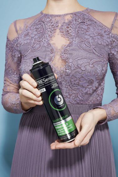 Hairspray guide: Woman holding TRESemme hairspray in her hands wearing a pale purple lace dress.