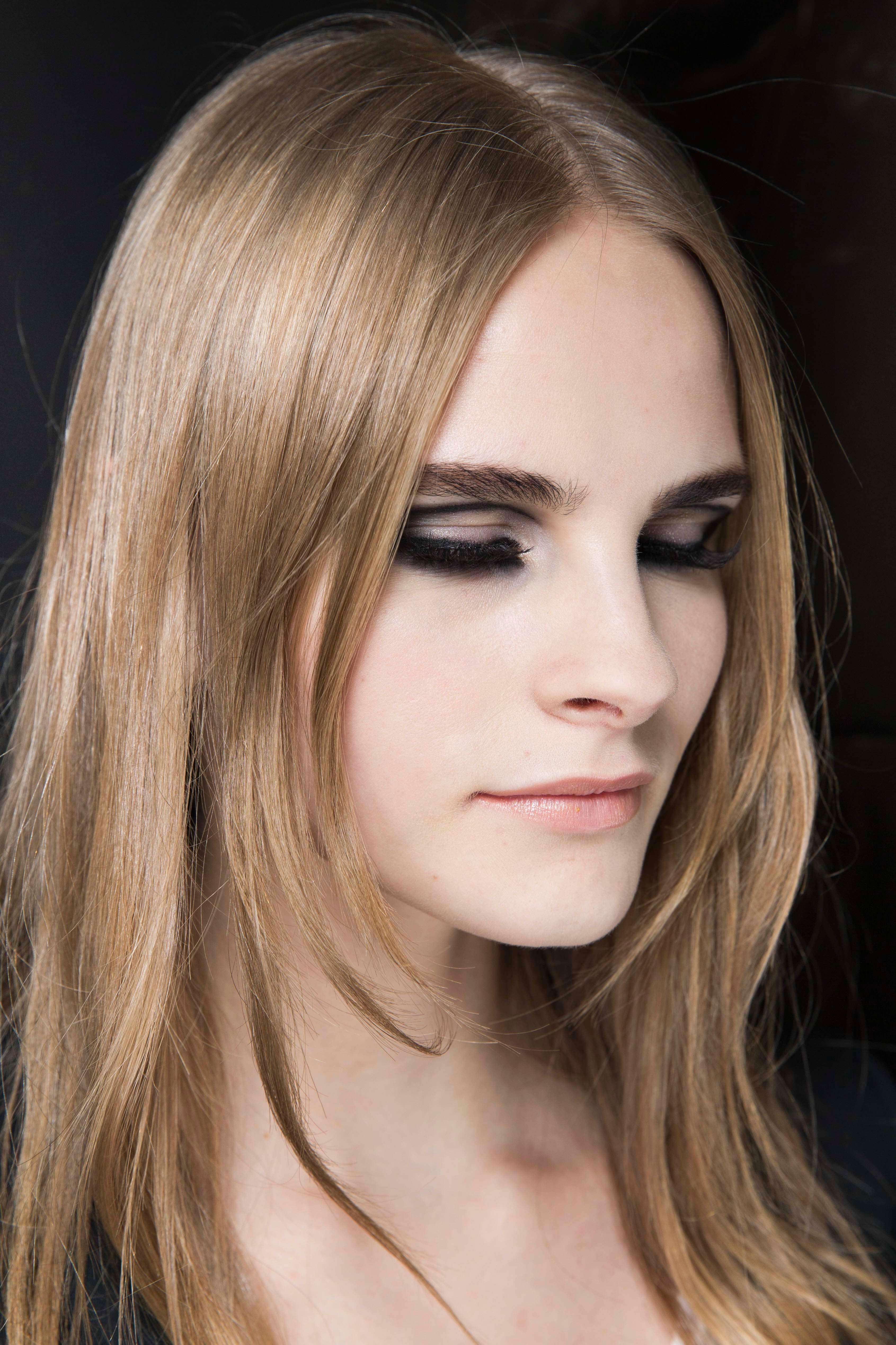 long layered haircuts: close-up of a dirty blonde model with wispy feathered layers