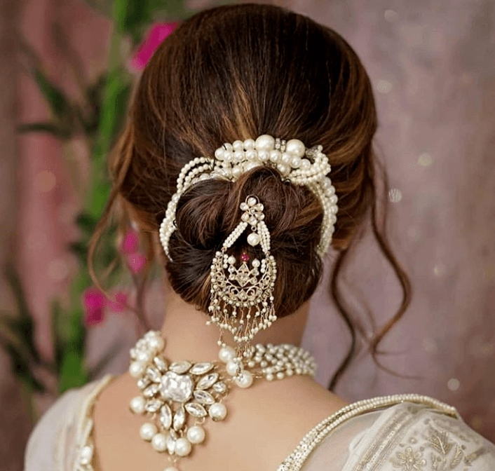 Indian hairstyles: Woman with honey brown hair styled into a low bun, decorated with Indian hair jewellery, posing in a studio