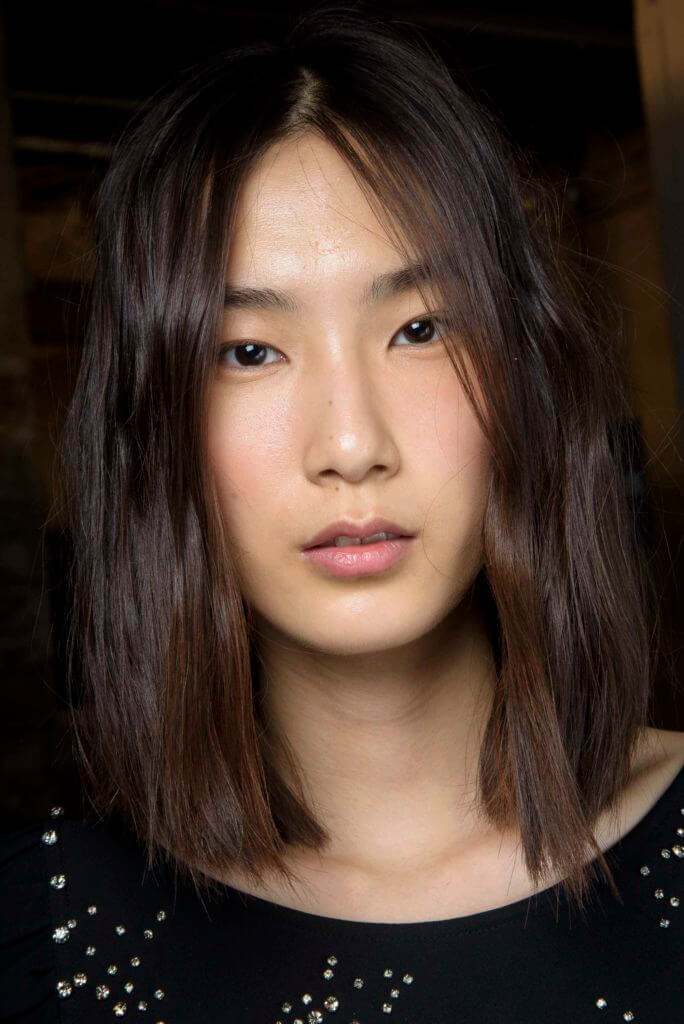 asian woman with dark brown hair cut into a blunt long bob and a middle parting