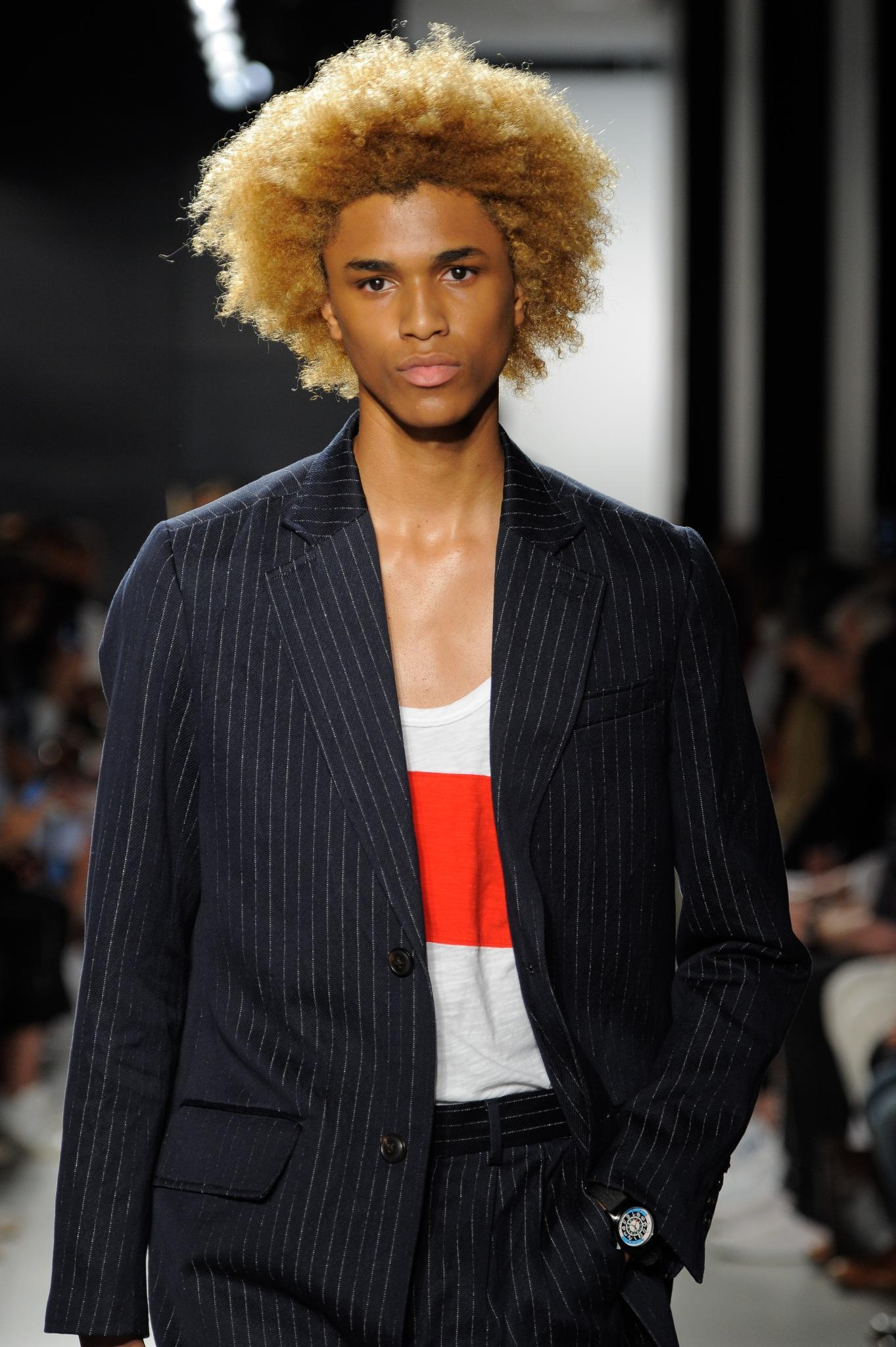 front view of male model on catwalk with bleach blonde big afro hair