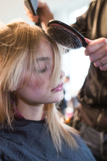 Blonde woman having her hair styled with a hair brush