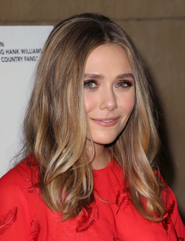 elizabeth olsen with a bronde hairstyle on the red carpet wearing a red dress