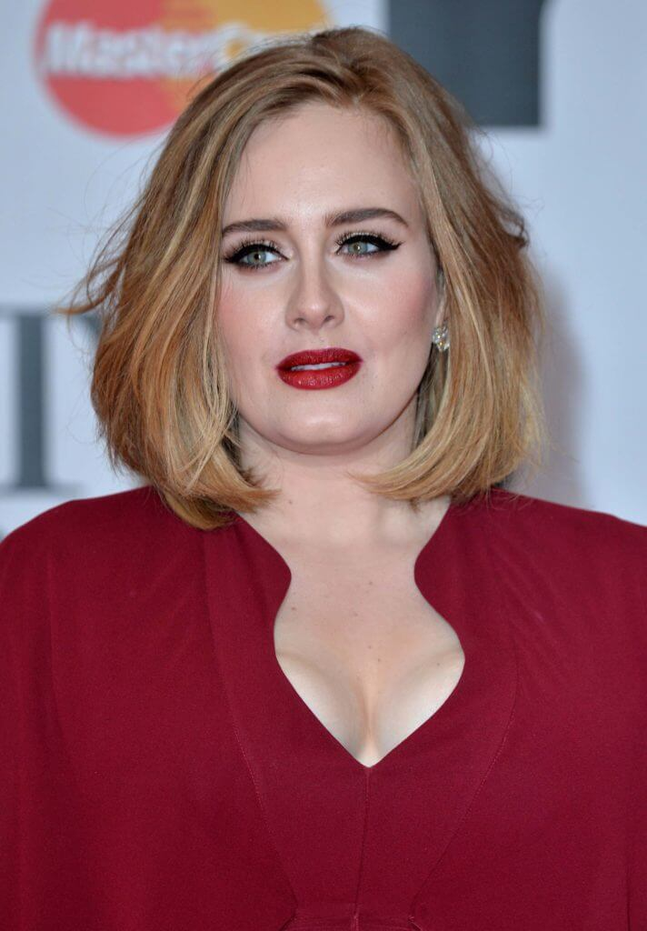 adele with a honey blonde bob wearing a deep red dress and matching lipstick on the red carpet