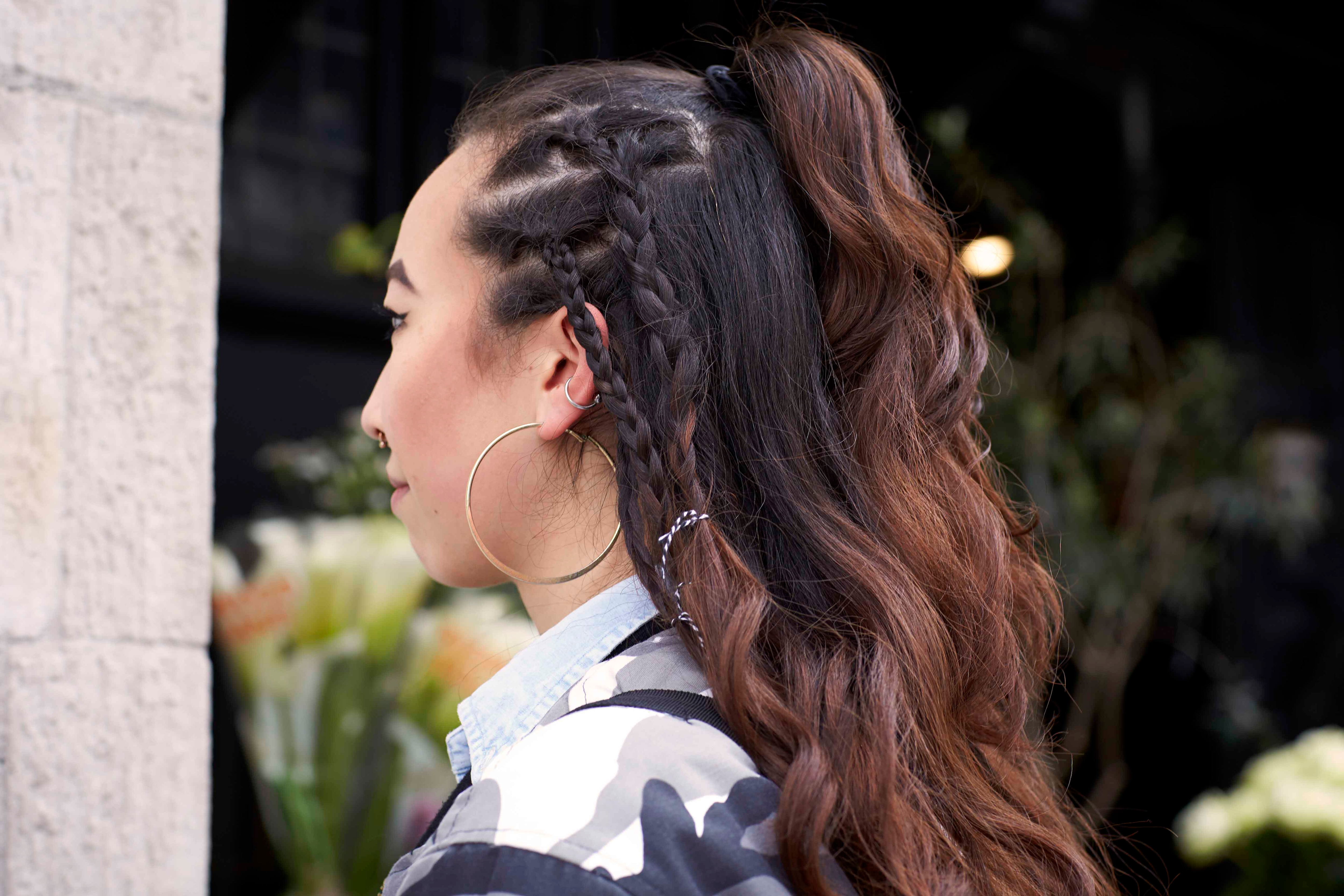 side view of woman with a half-up half-down plaited hairstyle