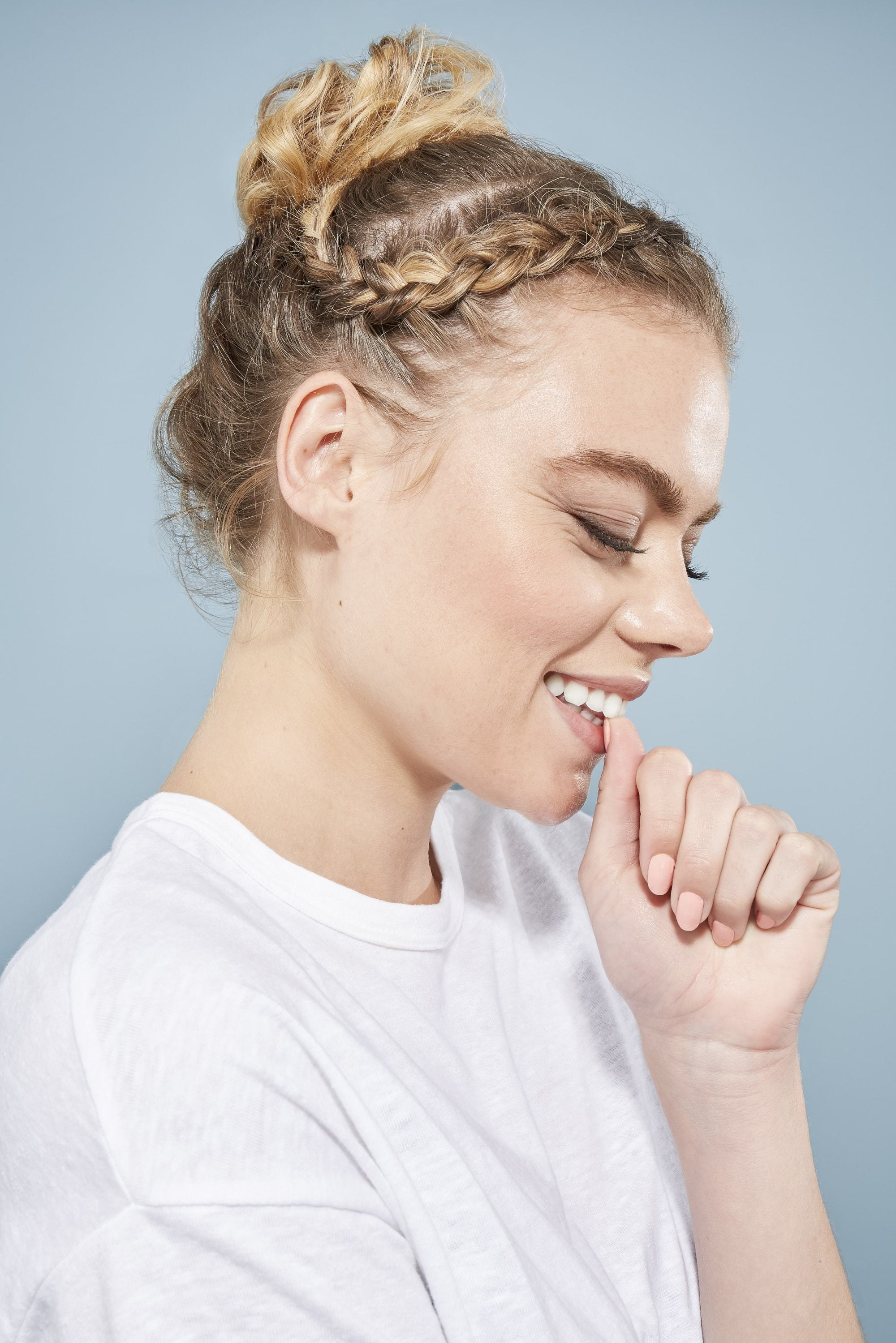 Updos with braids: Close up shot of a woman with headband braid into a messy bun updo.