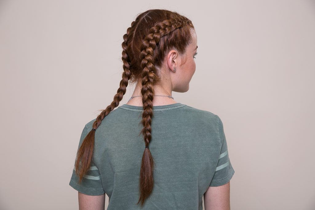 Updos with braids: Back shot of a woman with auburn braided pigtails hairstyle.
