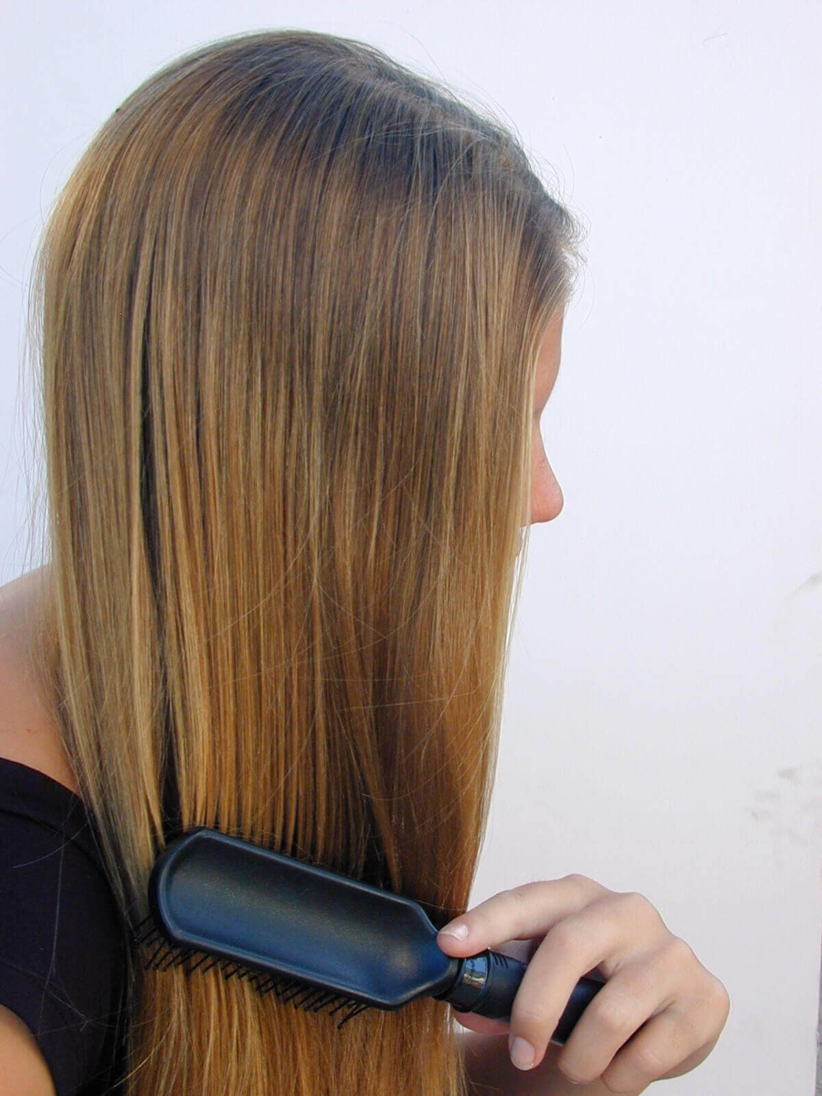 Light brown haired woman brushing her hair
