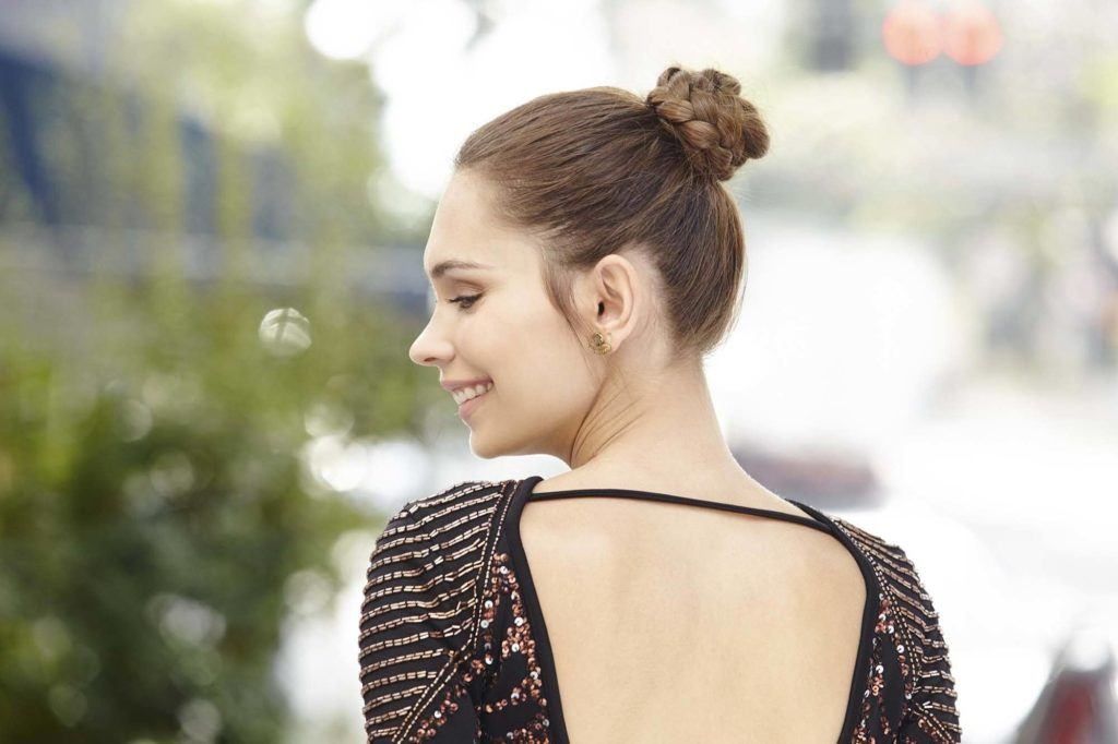 Updos with braids: Close up shot of a woman with medium brown hair styled into a braided topknot.