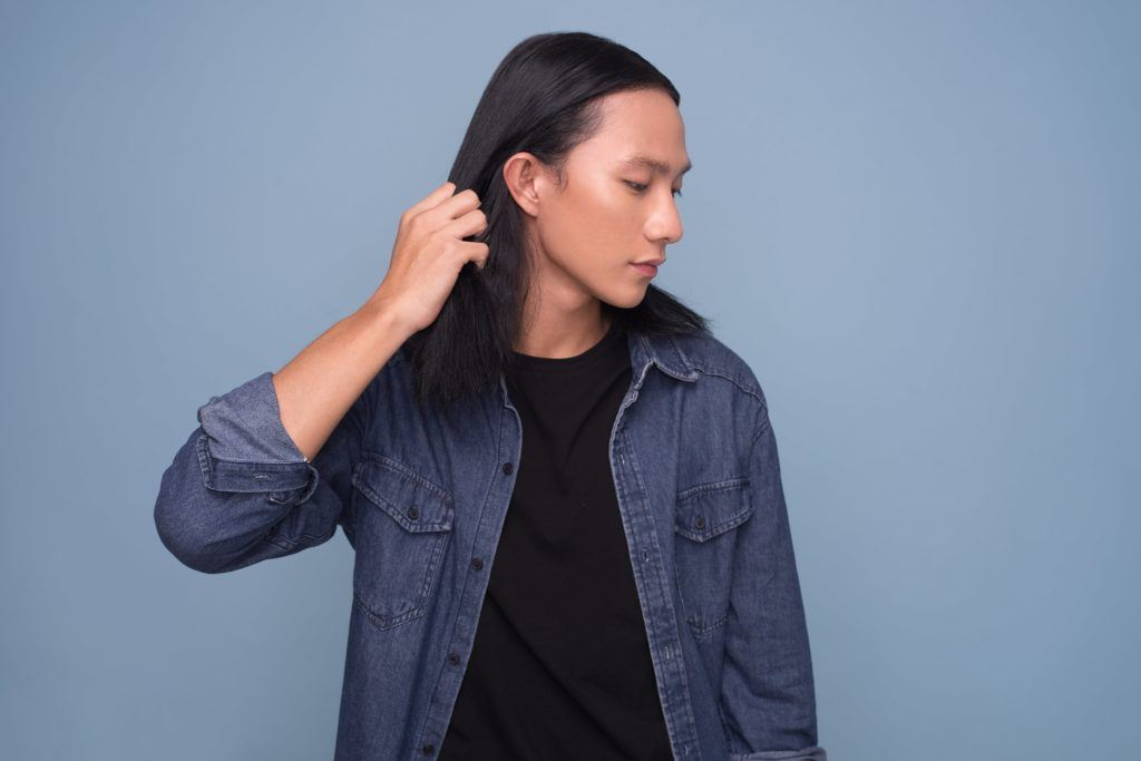 Asian men hairstyles: A young Asian man with shoulder-length straight hair