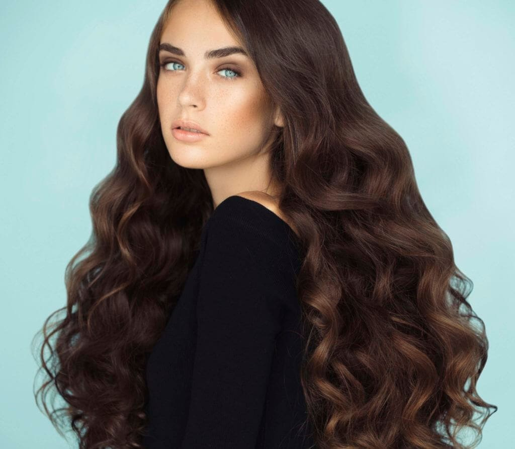 brunette model with long wavy hair against a blue background