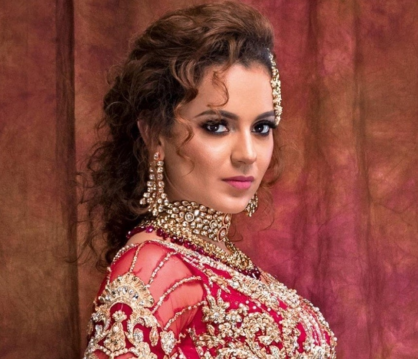 Indian hairstyles: Woman with chestnut brown medium hair styled into a curly updo, wearing traditional Indian clothing and posing in a studio