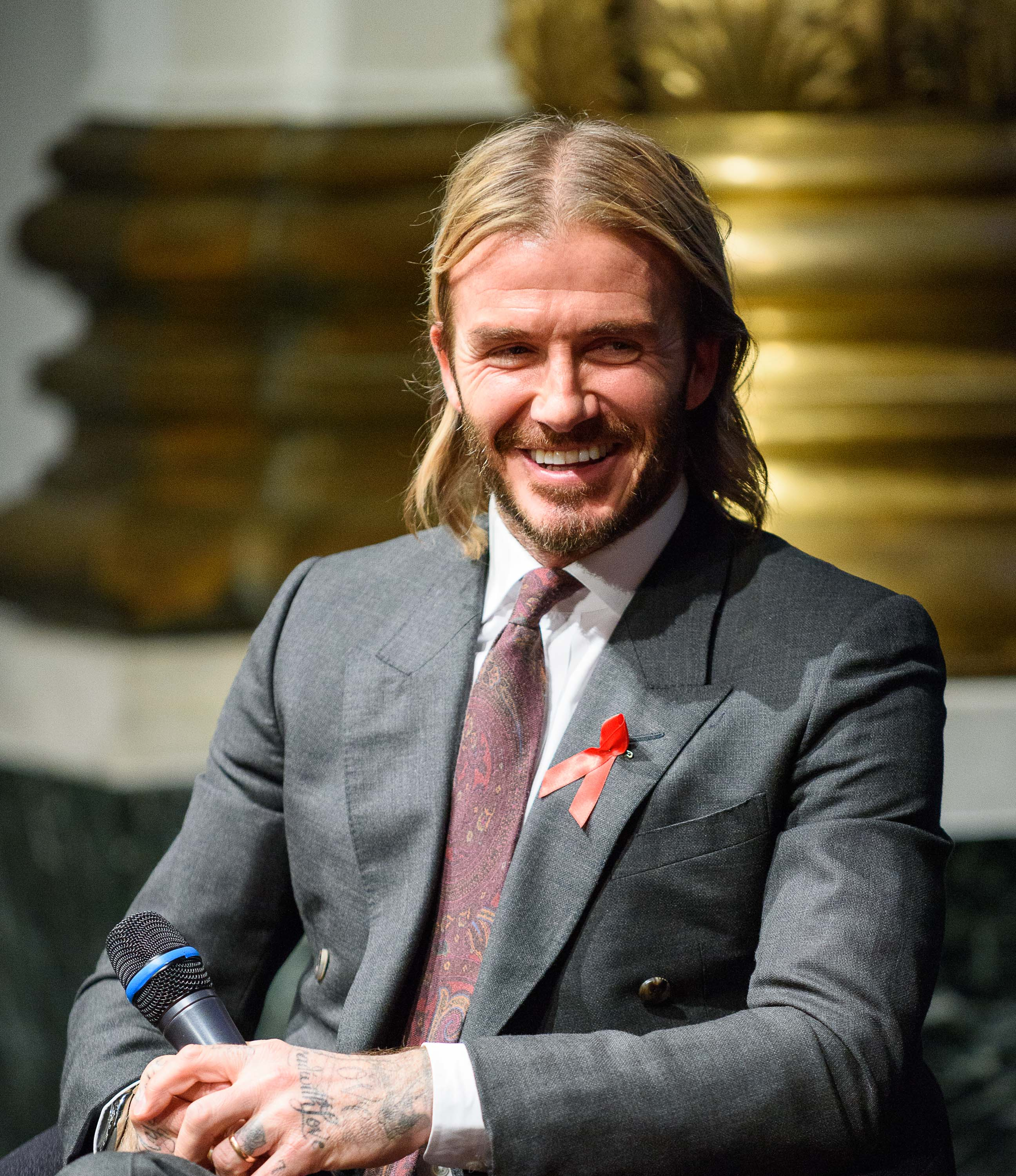 front view of david beckham with shoulder length highlighted blonde hair in middle parting