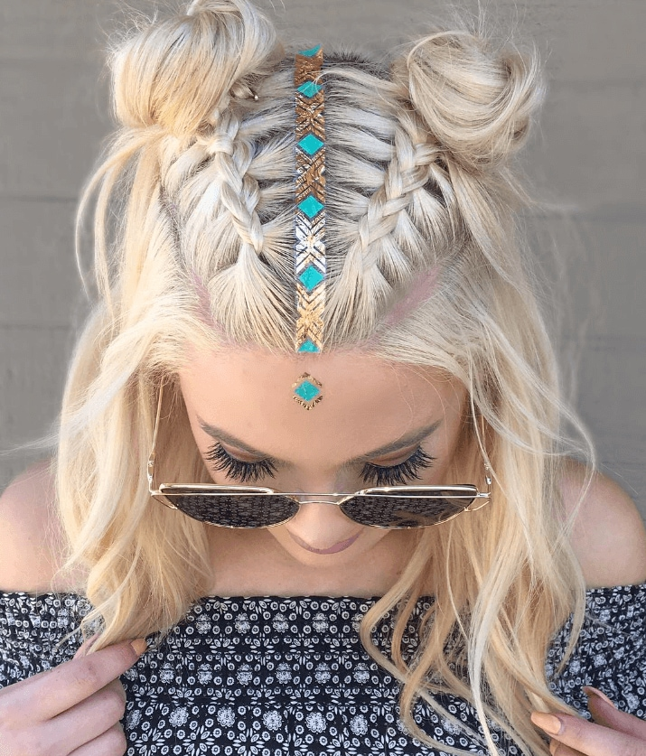 festival braids: close up shot of woman with platinum hair styled into a half-up, half-down braided space buns, with messy waves, wearing a bardot top and sunglasses