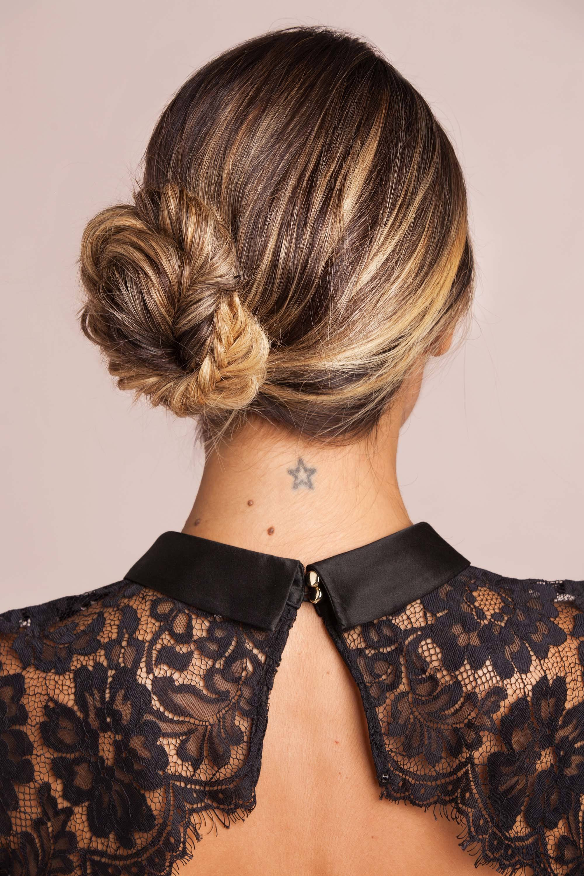 Updos with braids: Back shot of a woman with brown bronde hair styled into a side fishtail braided bun.