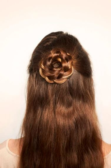back view of model with brown hair and a half-up flower braid