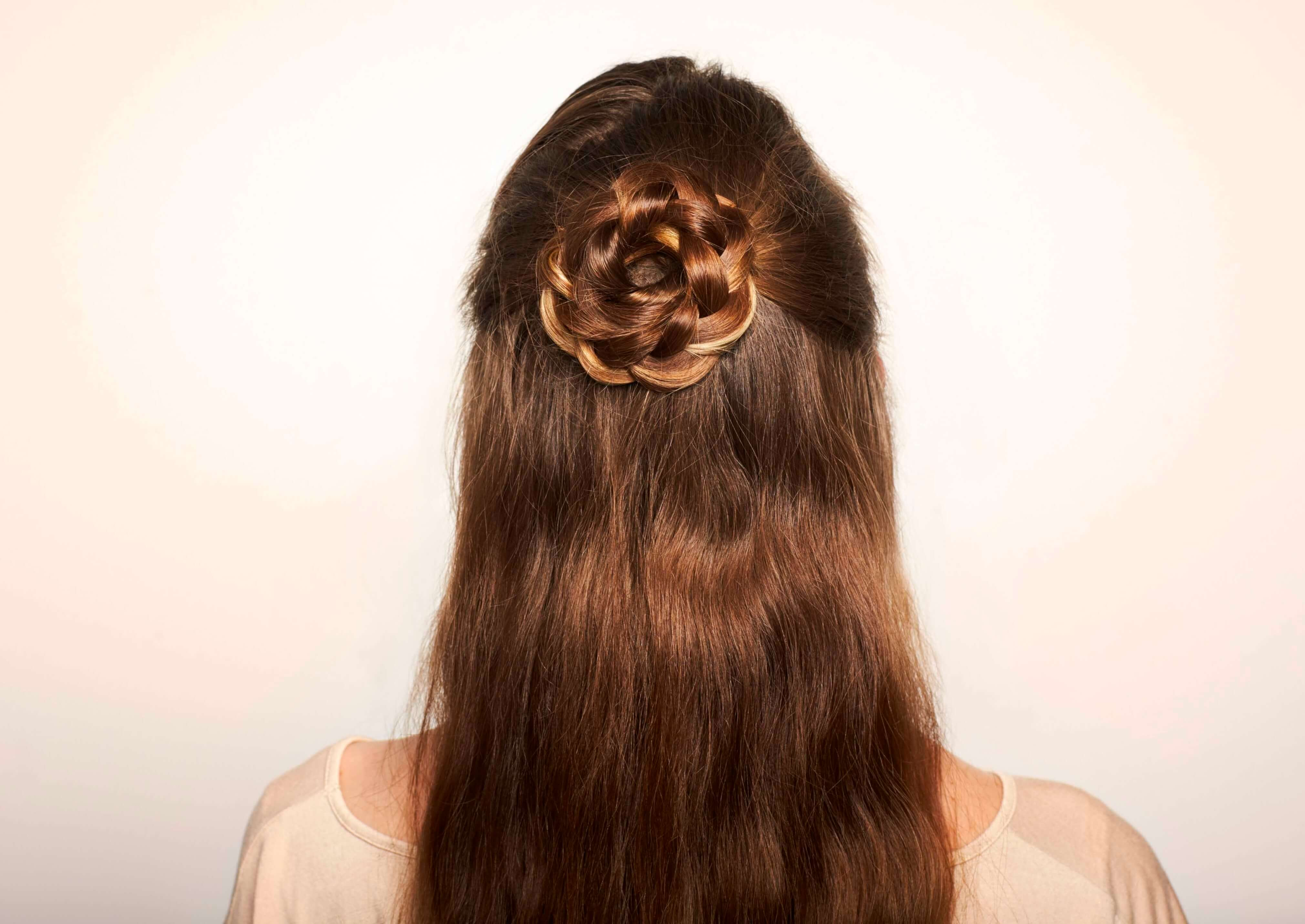 girl with long brown hair wearing a flower braid hairstyle