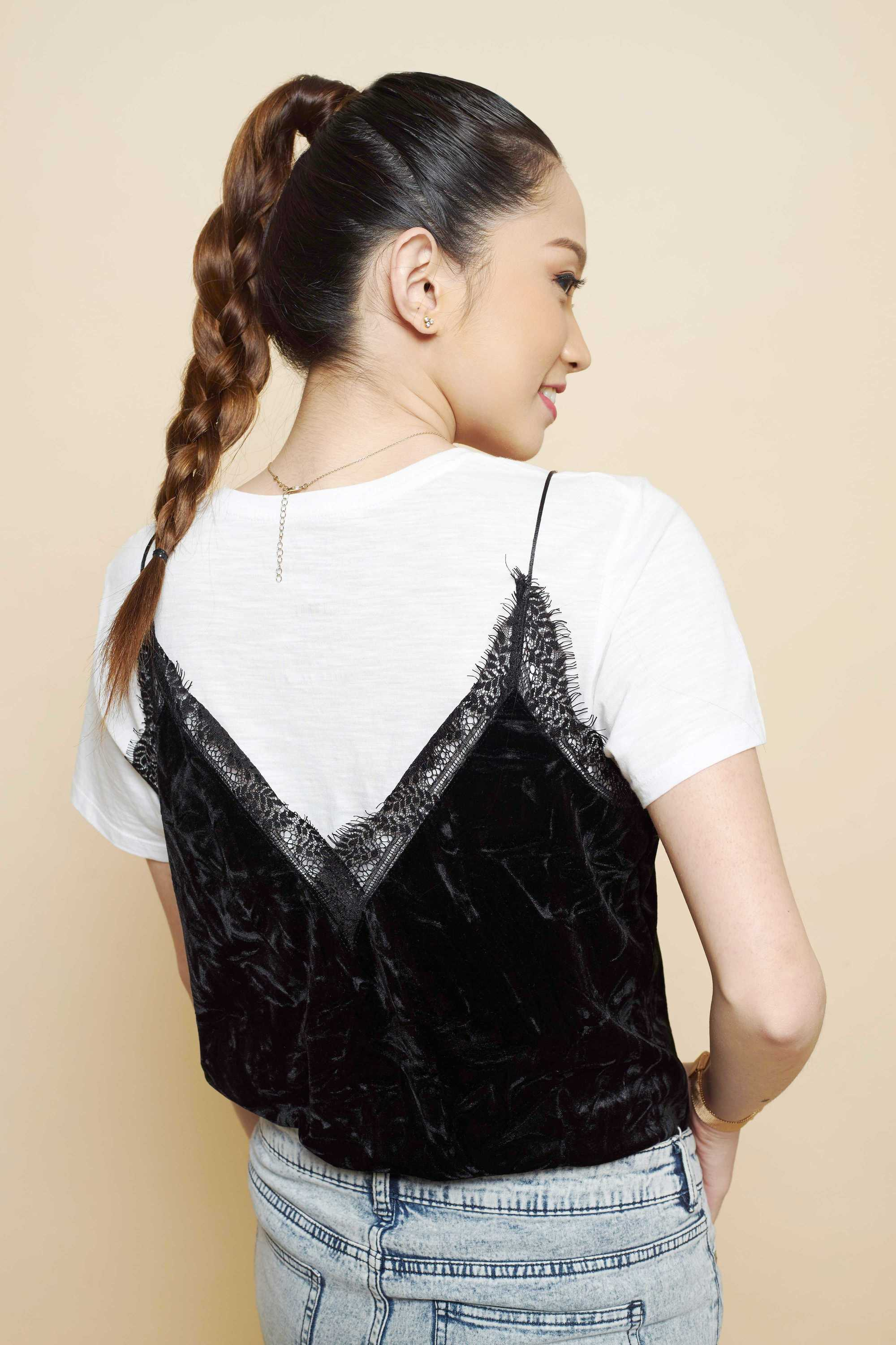 Updos with braids: Side shot of a woman with dark brown ombre hair styled into a four strand braided ponytail.