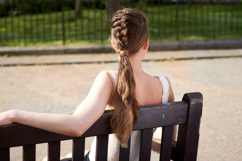 French braids: the back view of a young woman sitting on a bench with a French plait ponytail