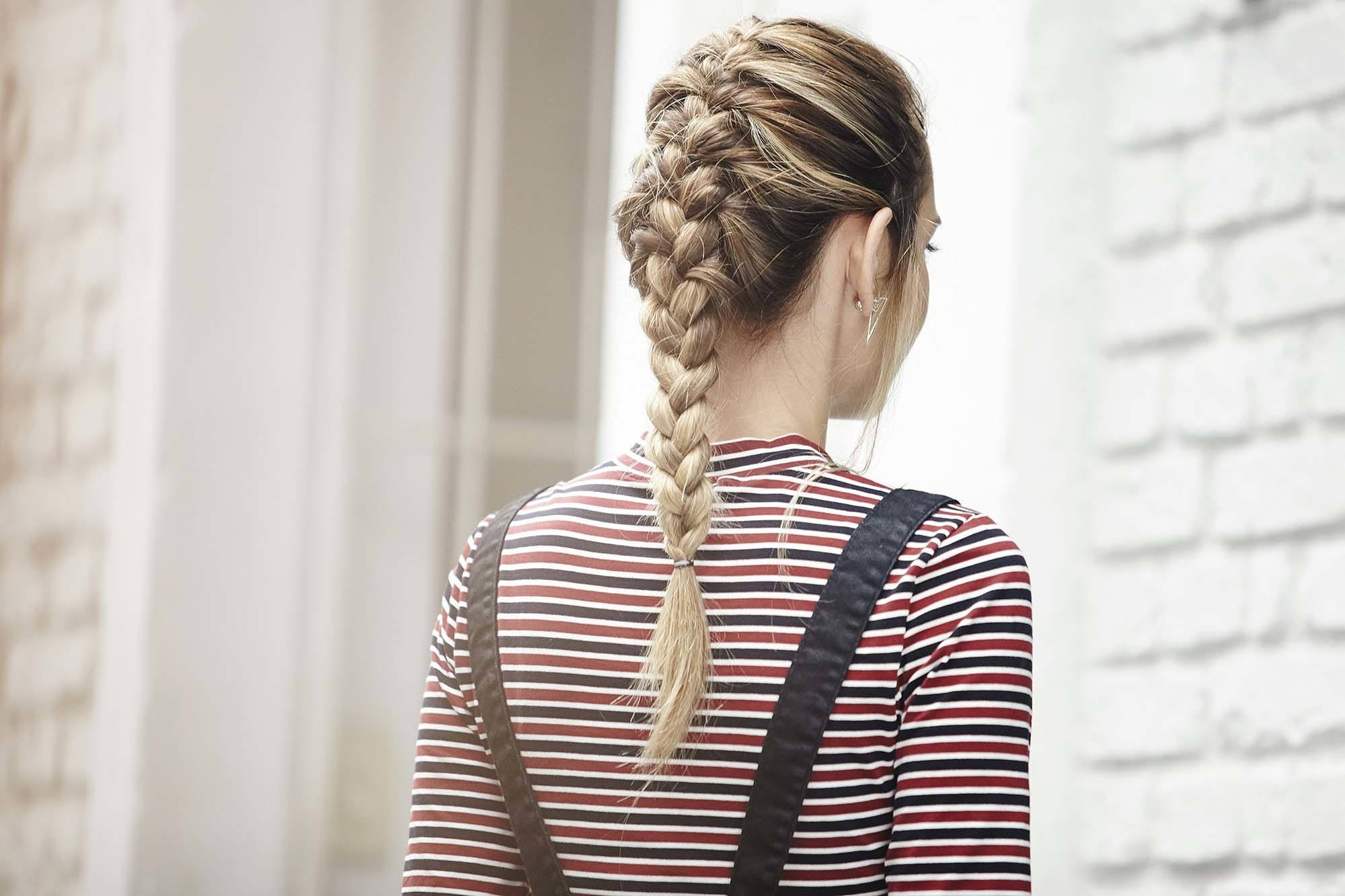 Updos with braids: Back shot of a woman with bronde hair styled into a French braid.